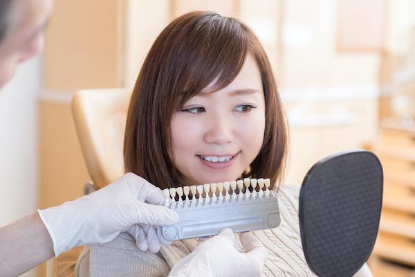 馬車道アイランドタワー歯科 院長ブログ 歯の詰め物・被せ物を徹底解説! 歯の被せ物の色を選ぶ女性の画像